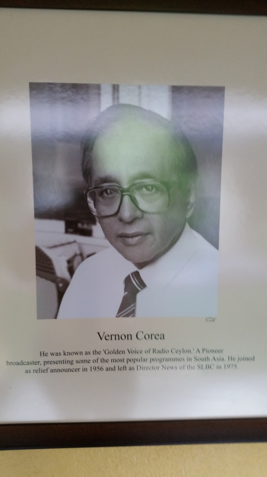 A Photograph of the pioneering broadcaster Vernon Corea who was known as the 'Golden Voice of   Radio Ceylon,' now hangs in the corridor of the Sri Lanka Broadcasting Corporation. (Radio Sri Lanka) A Presentation was made to the SLBC Chairman Hudson Samarasinghe who knew Vernon very well.